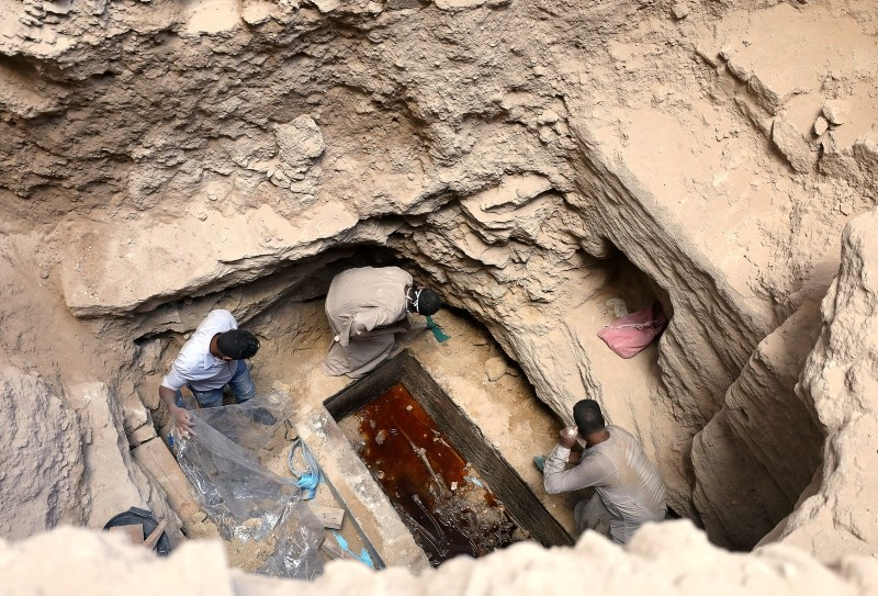 Archaeologists unearth coffin containing three mummies with sewage water and bones inside, in Alexandria, Egypt July 19, 2018. (Reuters Photo)