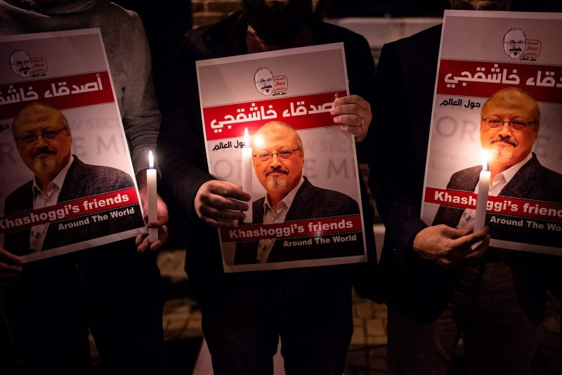 People hold posters picturing Saudi journalist Jamal Khashoggi and candles during a gathering outside the Saudi Arabian consulate in Istanbul, on Oct. 25, 2018. (AFP Photo)