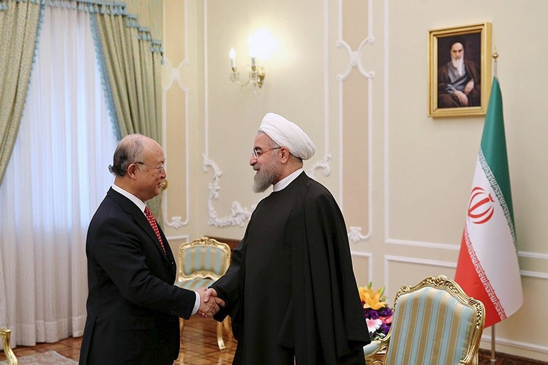IAEA) Director General Yukiya Amano (L) shakes hand with Iran's President Hassan Rouhani during their meeting in Tehran (Reuters Photo)