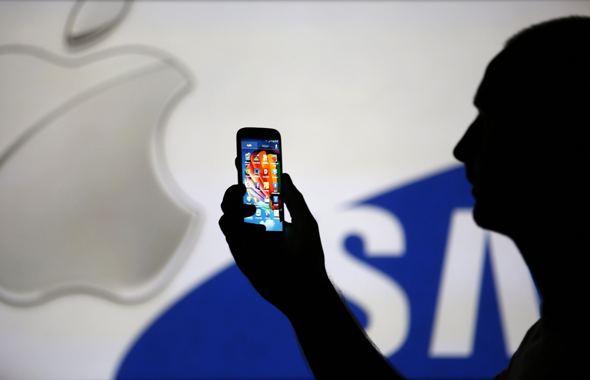 A man is silhouetted against a video screen wu0131th Apple and Samsung logos as he poses with a Samsung S4 smartphone in Zenica, on August 14, 2013. (REUTERS Photo)