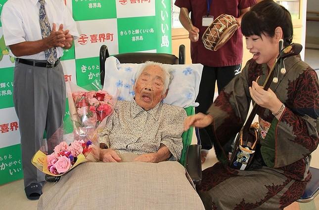 This picture received from Kikaicho Town Hall via Jiji Press, shows 117-year-old Nabi Tajima (2nd L) in Kikaicho on Kikai island of Kagoshima prefecture. (AFP Photo)
