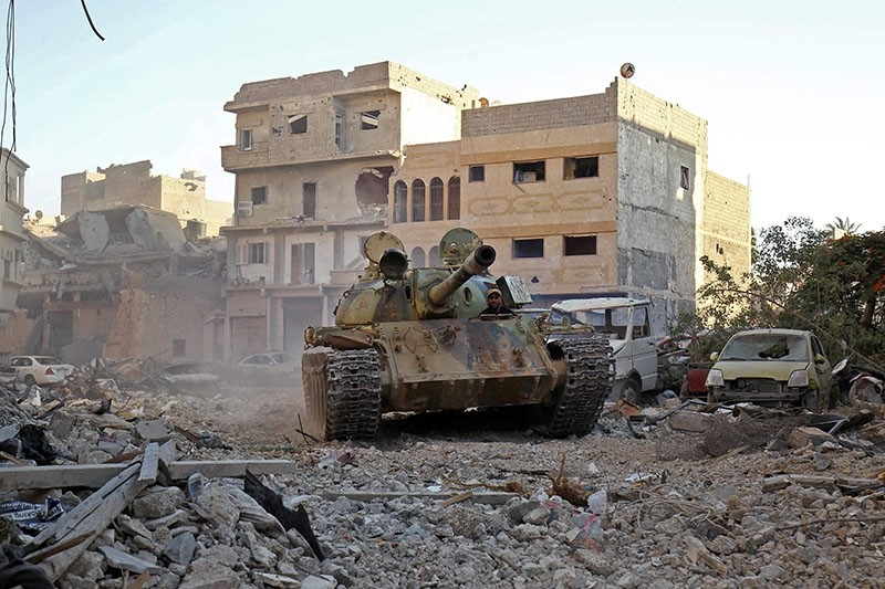 A member of the self-styled Libyan National Army, loyal to the country's east strongman Khalifa Haftar, rides in a tank as it drives down a street through the rubble in Benghazi's central Akhribish district on July 19, 2017. (AFP Photo)
