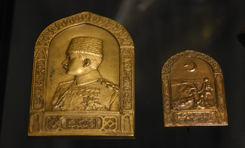 An embossment from WWI with the silhouette of Enver Pasha (on the left), and another embossment depicting an Ottoman soldier and a star and crescent (on the right).