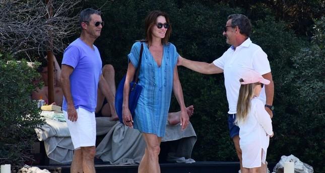 Бывший президент Франции Николя Саркози (справа) и его жена итало-французская певица Карла Бруни (в центре) на отдыхе в Бодруме. (Фото: IHA)