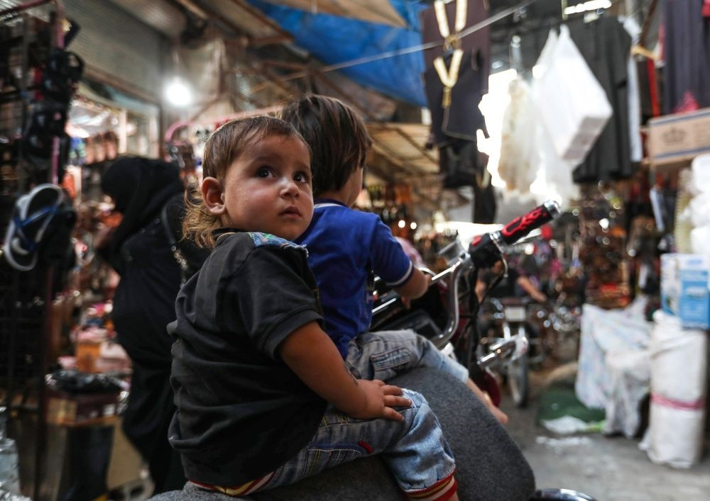Syrian children sit on a motorcycle at a market in the opposition-held Idlib province, Sept. 27.