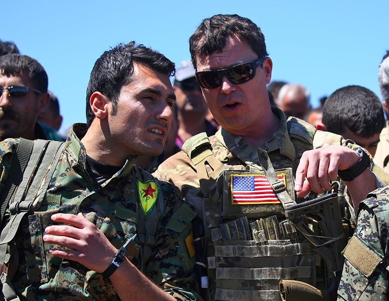 This file photo taken on April 25, 2017 shows a US-led coalition officer, speaking with a militant from the YPG at the site of Turkish airstrikes near northeastern Syrian town of Derik, known as al-Malikiyah in Arabic, on April 25, 2017. (AFP Photo)