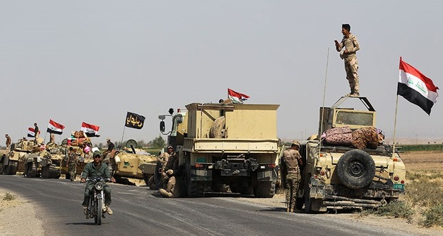 Iraqi forces rest on the road as they drive towards peshmerga positions on October 15, 2017, on the southern outskirts of Kirkuk (AFP Photo)