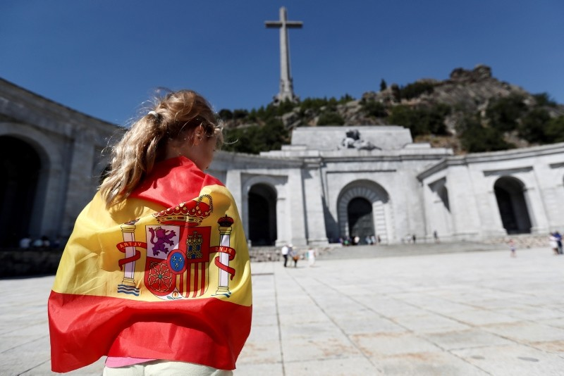 A woman is wrapped in a Spanish national flag on the esplanade of the El Valle de los Caidos (The Valley of the Fallen) memorial complex in the town of San Lorenzo del Escorial, 40 kilometers from Madrid, Spain, 21 August 2018. (EPA Photo)