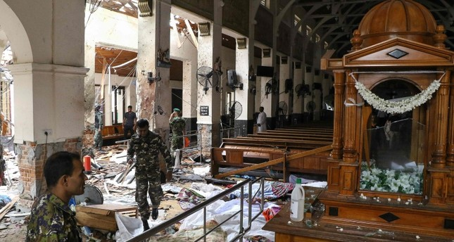 / Sri Lankan security personnel walk past dead bodies covered with blankets amid blast debris at St. Anthony's Shrine following an explosion in the church in Kochchikade in Colombo on April 21, 2019 (AP Photo)