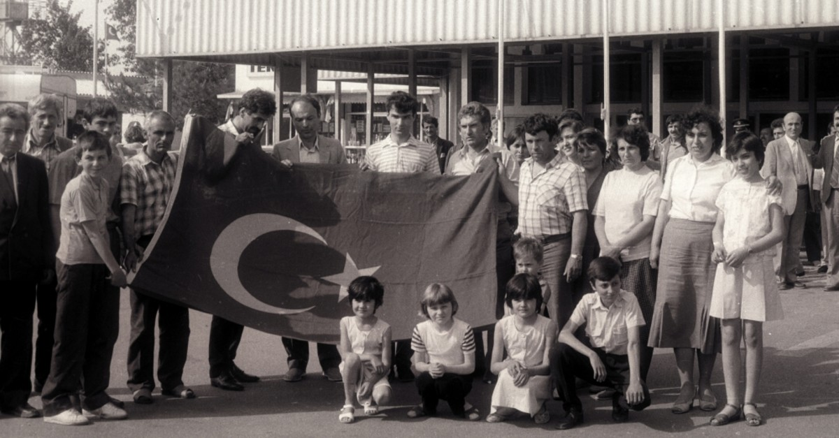 Turkish migrants from Bulgaria pose with a large Turkish flag after they arrive in Turkey through the u0130psala border crossing, June 6, 1989.