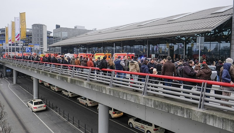 Travelers wait outside the Hamburg, northern Germany, airport Sunday, Feb. 12, 2017 after several people were injured by an unknown toxic that likely spread through the airport's air conditioning system. (AP Photo)