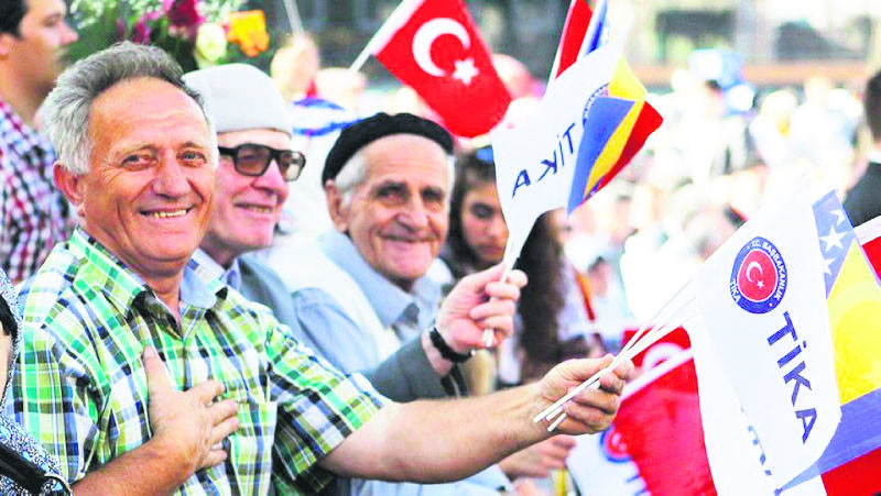 People wave Turkish and Bosnian flags at an opening ceremony for a project by the Turkish Cooperation and Coordination Agency (Tu0130KA) in Bosnia.