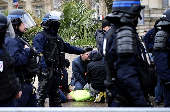 Policemen detain a protester during a demonstration of high school students in front of the Prefecture of Lille, northern France. (AFP Photo)