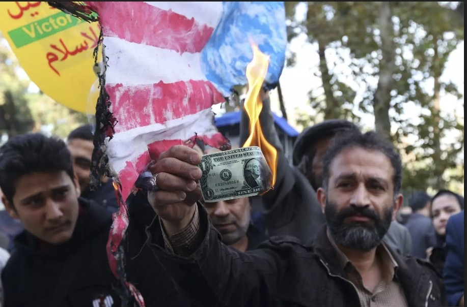 An Iranian protester burns a dollar banknote during a demonstration outside the former US embassy in Tehran, Iran on Nov. 4.