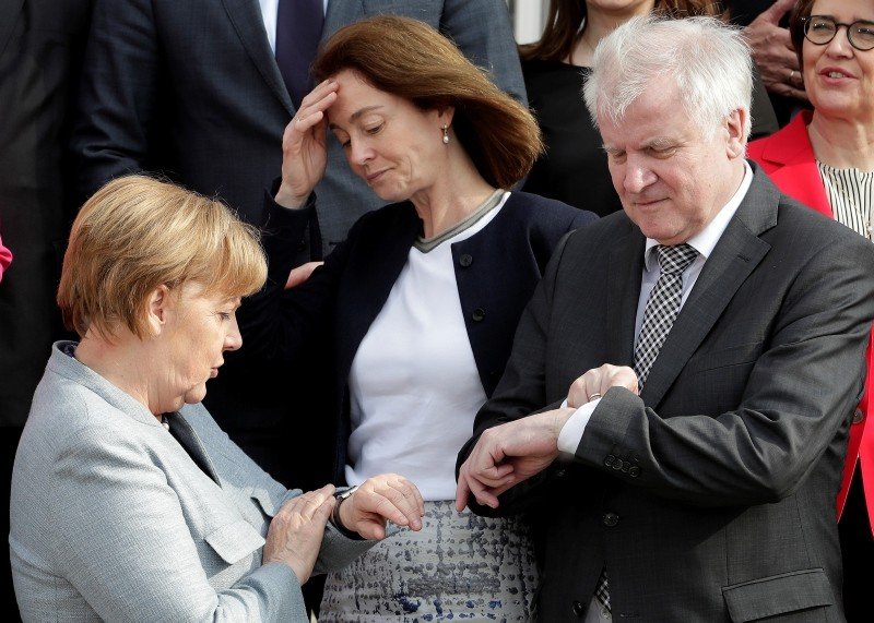 Chancellor Angela Merkel (L) and Interior Minister Horst Seehofer look at their watches after they and other members of the gov't posed for a group photo during a two-day retreat at the Meseberg Castle in Gransee, Germany, April 10, 2018. (AP Photo)