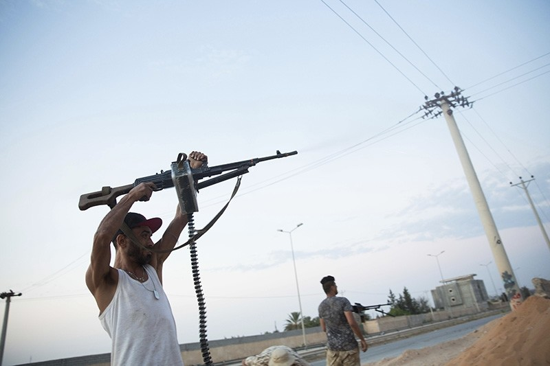 Fighters under the U.N.-backed government shooting on the front lines during clashes in southern Tripoli, Friday, Sept. 21, 2018. (AP Photo)