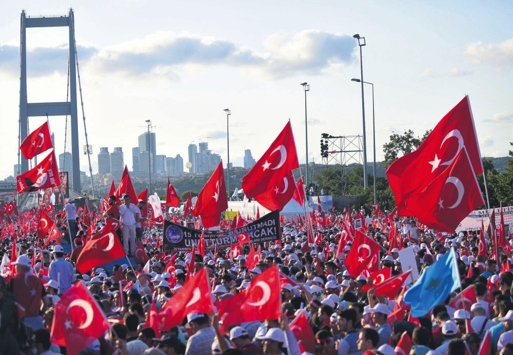 People wave Turkish flags as they stand near the July 15 Martyrs Bridge to commemorate the first anniversary of the bloody coup attempt, Istanbul, July 15.