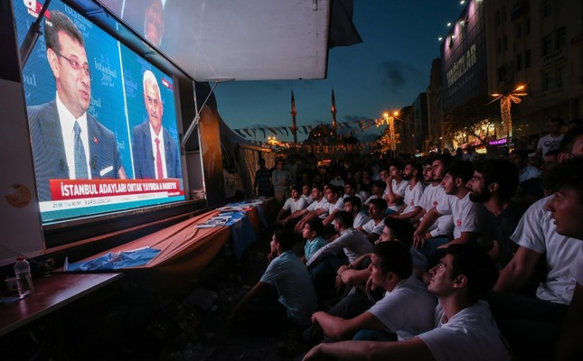 Spectators watch the live debate between the two major metropolitan municipality candidates in Istanbul's Esenler district, June 17, 2019.