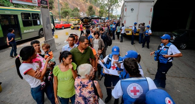 People queue to receive drums to collect water and water purification tablets from members of the Venezuelan Red Cross in Caricuao neighborhood in Caracas, Venezuela, on April 16, 2019. (AFP Photo)
