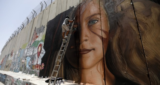 A foreign artist paints a mural of Palestinian Ahed Tamimi on the Israeli separation wall in the West Bank city of Bethlehem, 25 July 2018. (EPA Photo)