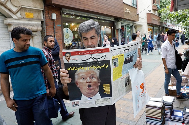 An Iranian man reads a copy of Iranian daily newspaper 'Arman' with a picture of US President Donald Trump on its front page with the title in Persian that reads 'Crazy Trump and logical JCPOA' on display in Tehran, Iran, 14 October 2017. (EPA Photo)