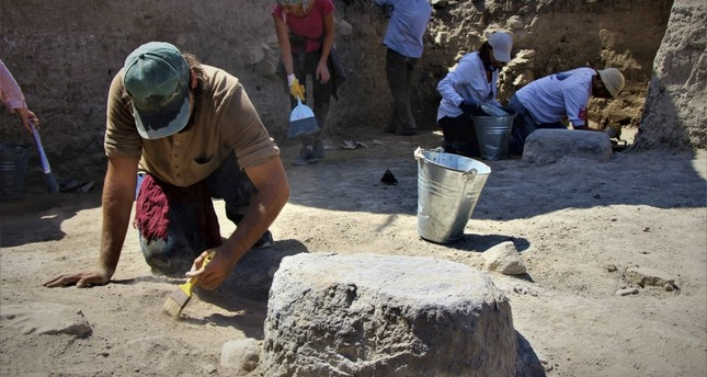 A photo showing  the excavation of the Persian palace's columns.