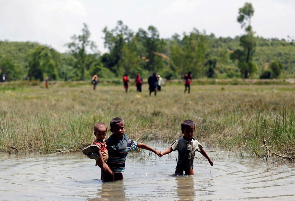 Rohingya children make their way through water as they try to reach the Bangladeshi side from no man's land.