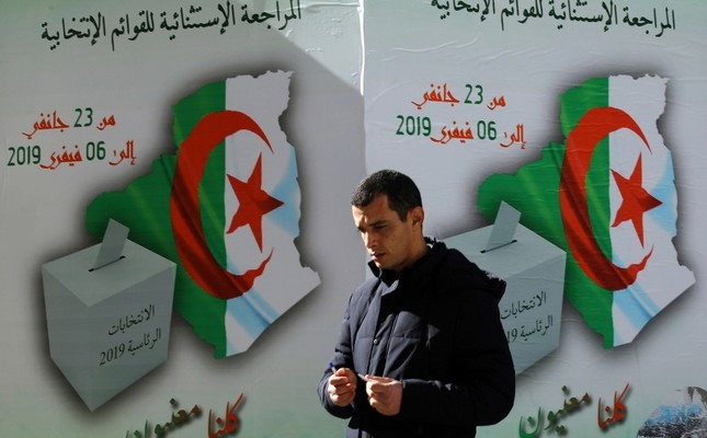 In this Feb. 5, 2019, photo, a man walks past a poster asking citizen to register to vote in Algerian capital of Algiers. (AP Photo)
