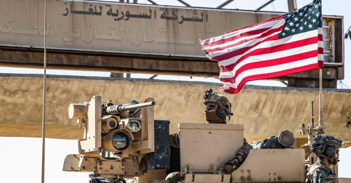 A U.S. soldier mans a turret in an armored vehicle near a sign reading the ,Syrian Gas Company, in Arabic in Rumaylan, Syria, Nov. 6, 2019. (AFP Photo)