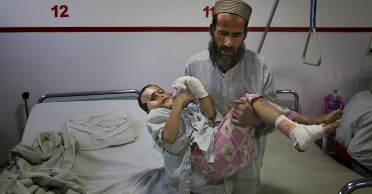 In this Thursday, Dec. 12, 2019, photo, Ismatullah carries his 9-year-old son Eimal, who has lost his right eye and several fingers on his hands in a landmine blast, at Emergency Surgical Center for Civilian War Victims in Kabul, Afghanistan. (AP Photo)