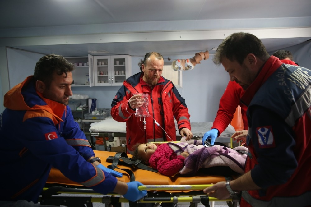 Paramedics attend a sick Syrian child at a clinic near the Turkish-Syrian border.  Along with health services offered at Turkish hospitals, healthcare staff is deployed to the country's border with Syria.