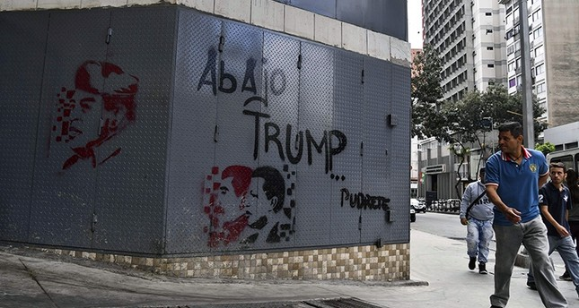 A man walks near a grafitti depicting late Venezuelan president Hugo Chavez (R and L), President Nicolas Maduro (C) with a legend reading down with Trump in Caracas, on Jan. 24, 2019. (AFP Photo)