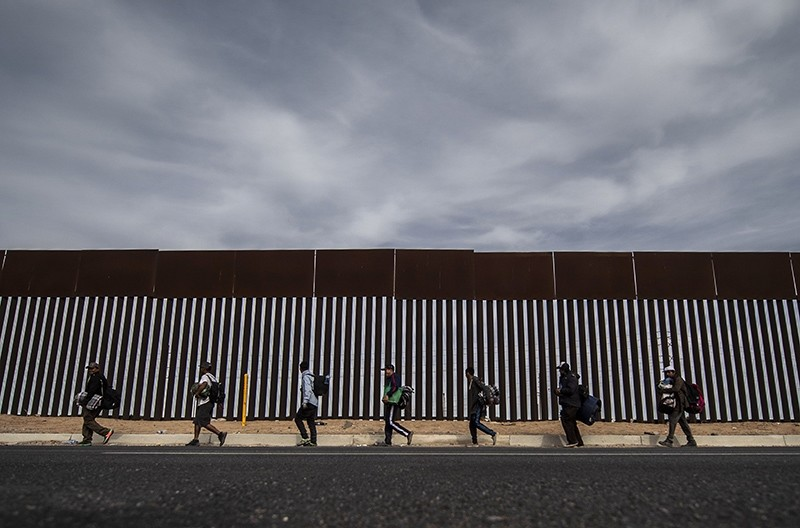Central American migrants moving in a caravan toward the United States walk along the metal fence on the border between Mexicali in Mexico's Baja California State, and Calexico, in California, on Nov. 19, 2018. (AFP Photo)