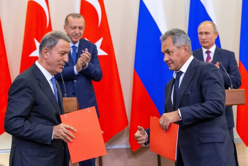 Russian Defense Minister Sergei Shoig (foreground R) and Defense Minister Hulusi Akar shake hands as Russian President Putin (R)  and President Erdou011fan (2-L) look on during their joint news conference on Sept 17. (EPA Photo)