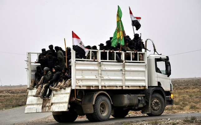 Fighters of Iraqi Shiite militias who volunteered to support the Iraqi forces ride a truck as they make their way towards Daquq town near Tikrit city, northern Iraq, 08 February 2015. (EPA Photo)