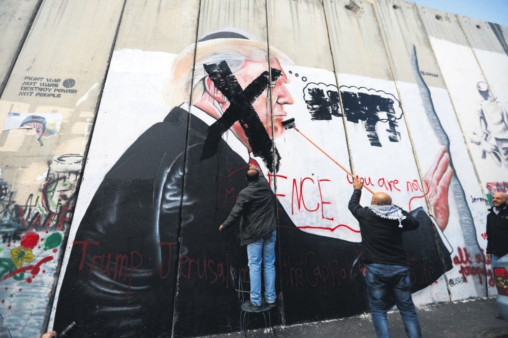 Palestinians paint an X over the face of a picture of President Trump that was painted on the Israeli separation wall in Bethlehem, West Bank, during protests against Trump's decision to recognise Jerusalem as the capital of Israel. Dec. 17.