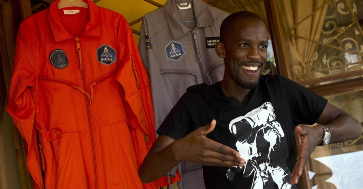 In this file picture taken on Jan. 9, 2014, Mandla Maseko speaks to a journalist in front of two NASA spacesuits in Mabopane, north of Pretoria. (AFP Photo)