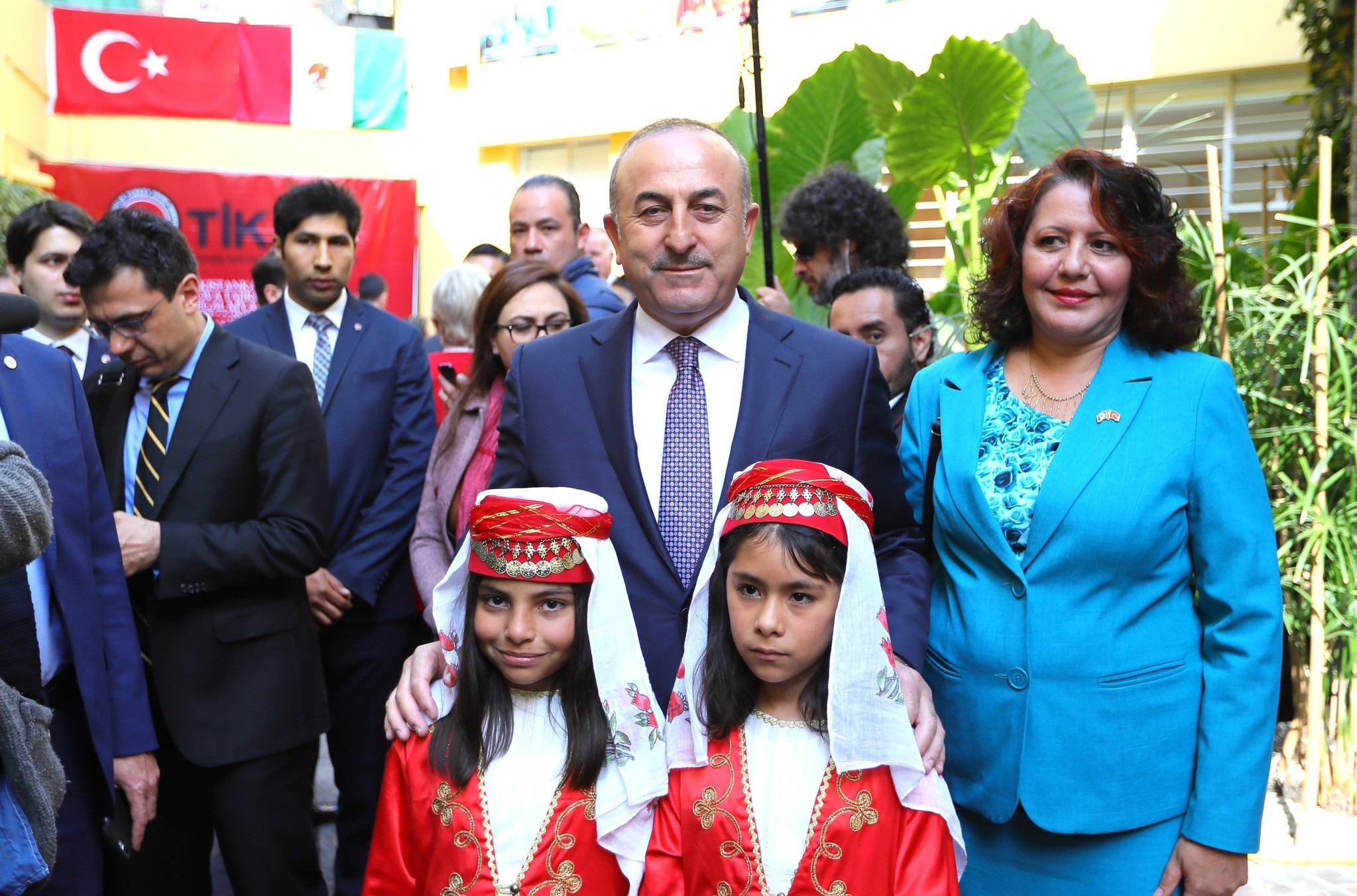 Foreign Minister Mevlu00fct u00c7avuu015fou011flu poses with two Mexican girls wearing traditional Turkish costume during the opening ceremony of TIKAu2019s Mexico office on February 3, 2017. (AA Photo)