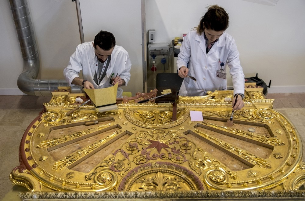Restorers work on a piece with gold leafs from a bed belonging to Sultan Abdu00fclaziz in the workshop in Istanbul, Feb. 14, 2019.