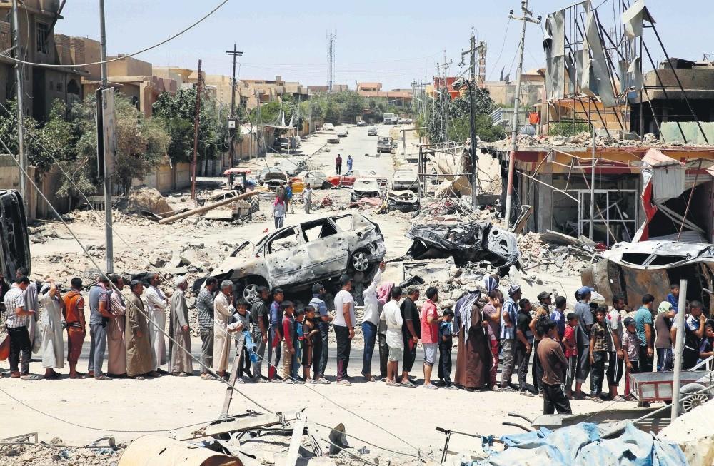 Iraqis stand in line to receive food aid in western Mosul's Zanjili neighborhood.