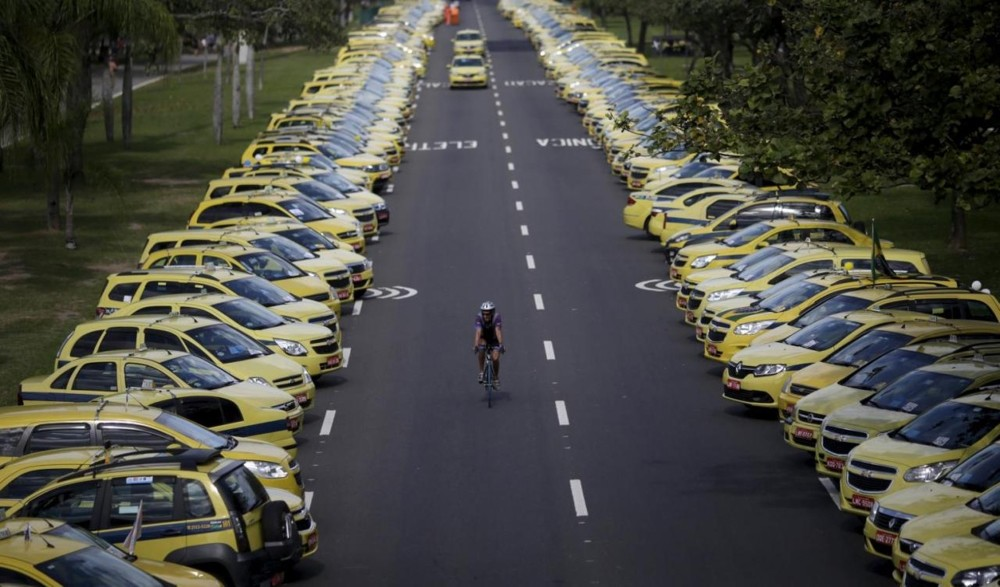 A man rides his bicycle between taxis parked on the street during a protest against the online ride-sharing service Uber in Rio de Janeiro, Brazil.