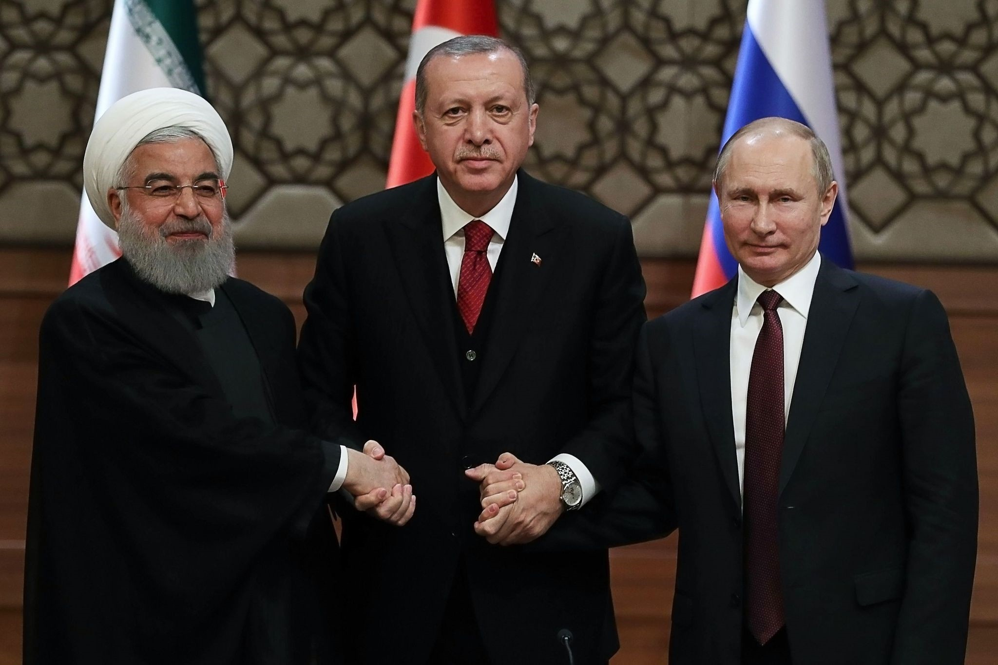 President Recep Tayyip Erdou011fan, Iran's President Hassan Rouhani, and Russia's President Vladimir Putin shake hands after a joint press conference as part of a tripartite summit on Syria, in Ankara, April 4.