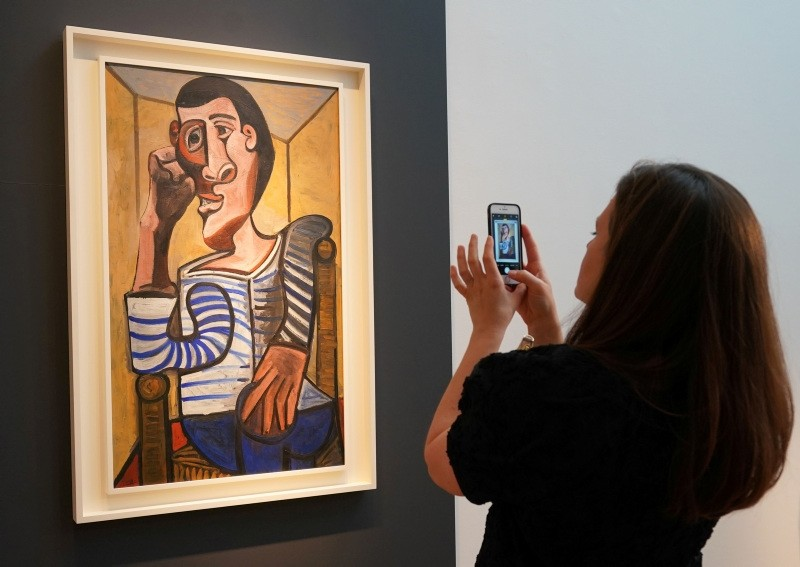 In this file photo taken on May 3, 2018 a Christie's employee takes a picture of Pablo Picasso's ,Le Marin, during a media preview at Christie's  in New York.  (AFP Photo)