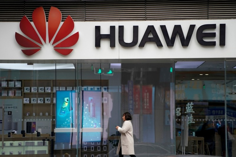A woman walks by a Huawei logo at a shopping mall in Shanghai, China December 6, 2018. (Reuters Photo)