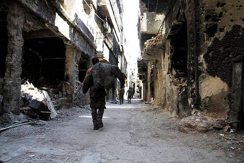 A man walks between damaged buildings in Yarmouk refugee camp located in a Damascus suburb. (File Photo)