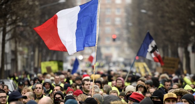 People hold up the French flag during a yellow vest demonstration in the northern French city of Lille, Dec. 29.