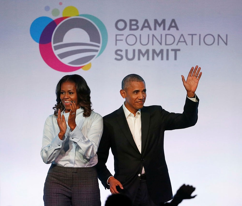 In this Oct. 13, 2017 file photo, former President Barack Obama (R), and former first lady Michelle Obama arrive for the first session of the Obama Foundation Summit. (AP Photo)