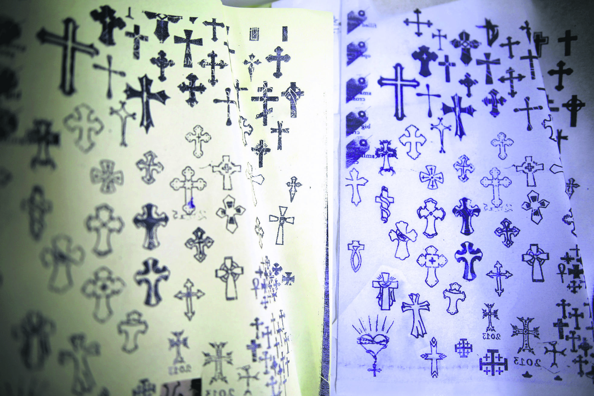 Pages displaying different Christian cross designs at the studio of tattoo artist Wassim Razzouk.