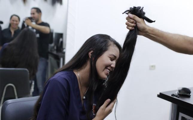 Valery Díaz holds the hair she had cut off to earn $100 in Caracas, April 5, 2019.