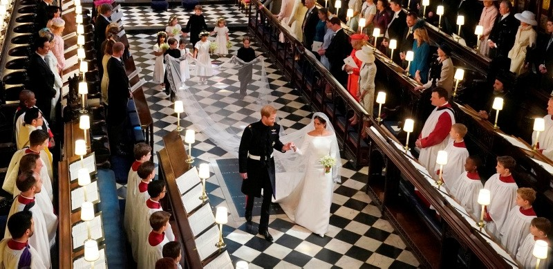 Britain's Prince Harry, Duke of Sussex (L) and Britain's Meghan Markle, Duchess of Sussex, (R) walk away from the High Altar toward the West Door to exit at the end of their wedding ceremony in St George's Chapel, Windsor Castle, in Windsor, on May 19, 2018.